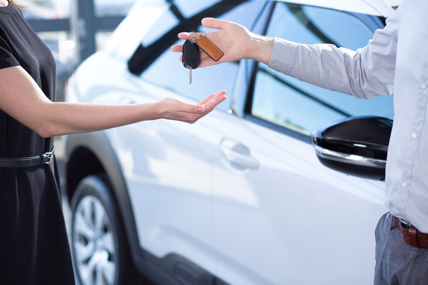Close-up of seller's hands with keys and buyer after transaction in car showroom